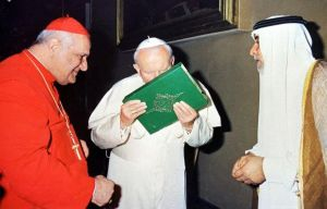Pope John Paul II kisses Koran in front of a Cardinal and a Muslim leader